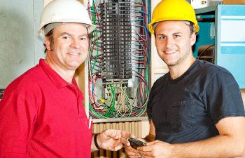 electrician and apprentice working on
