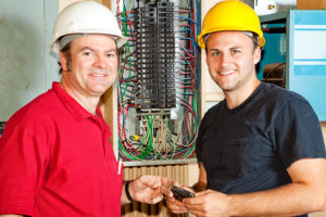 professional electrician and apprentice working on